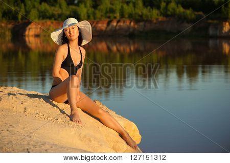 Asian woman in hat and bikini on sand