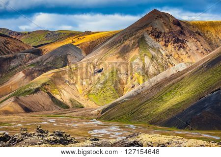 Travel to Iceland in the summer. National park Landmannalaugar. Multi-colored mountains from mineral rhyolite are lit with the July sun