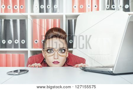 Business Woman With Big Eyes Hiding Behind Table