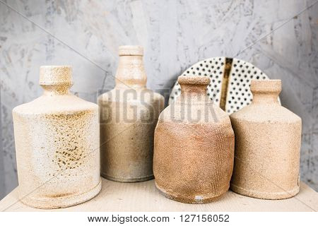 Antique clay decoration set  on white background. Many handmade ceramics objects on wooden shelf. Brown clay crockery in pottery workshop.
