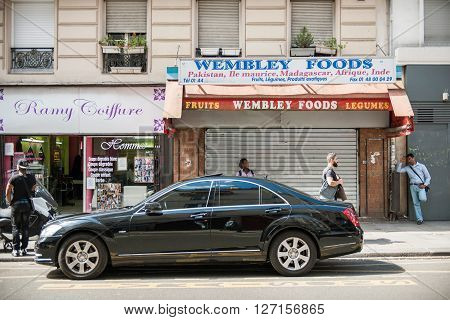 PARIS FRANCE - AUG 18 2014: Paris street with diverse African food stores hair saloon and luxury Mercedes limousine and pedestrian walking nearby on a summer sunny day