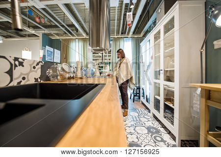 PARIS FRANCE - APR 12 2016: Woman choosing modern kitchen furniture and kitchen appliances in the modern IKEA shopping furniture mall in Paris
