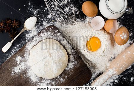 baking background with cake ingredients on black chalkboard from above bowl flour eggs