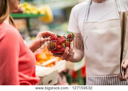 customer picking strawberries from salesman at street market