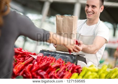 smiling salesman measuring pepper at the market
