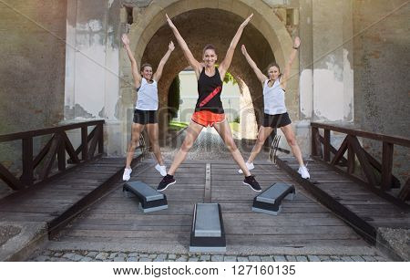 A group of women exercising outdoor on stepper smiling