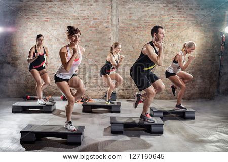 Sporty people on training on steppers, power step