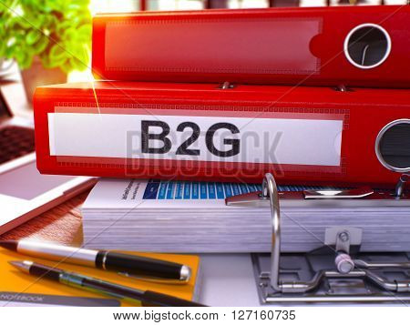 Red Office Folder with Inscription B2G on Office Desktop with Office Supplies and Modern Laptop. B2G Business Concept on Blurred Background. B2G - Toned Image. 3D Render.