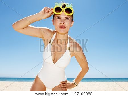 Woman In Pineapple Glasses Looking Into The Distance At Beach