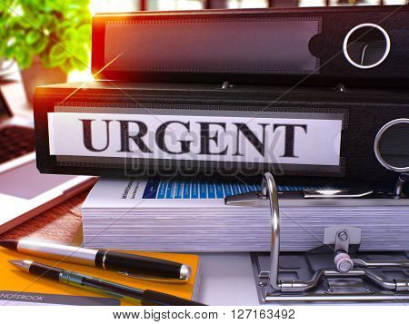 Black Office Folder with Inscription Urgent on Office Desktop with Office Supplies and Modern Laptop. Urgent Business Concept on Blurred Background. Urgent - Toned Image. 3D.
