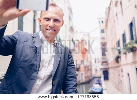 Smiling man take a selfie tourist photo on the Venice chanel background