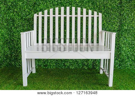 White single wooden chair on the grass in a garden