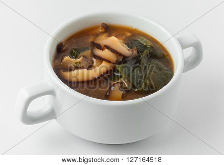miso soup pasta dark and light, wakame seaweed, shiitake mushrooms, tofu cheese, in white tureen on white background