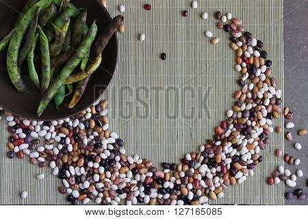 Colorful Swirl of Dried Beans on Placemat with Bowl of Bean Pods and room for text