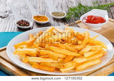 Tasty french fries on white dish on a cutting board with spices ketchup close-up view from above