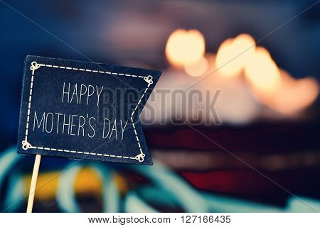 closeup of a black flag-shaped signboard with the text happy mothers day and a cake topped with lit candles in the background