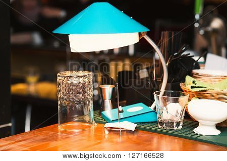 Table lamp on the bar. Empty glass on the bar background. Quiet evening in the bar. Alcohol party at the bar. Before party