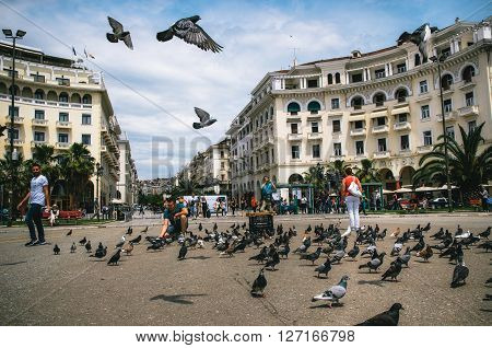 THESSALONIKI, GREECE - MAY 27, 2015:  People at famous Aristotelous Square . A man feeds pigeons.