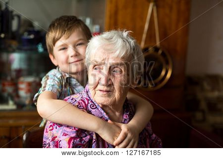 Portrait of an elderly woman with a small grandson in the background.