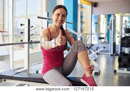 Smiling woman sitting on the bench and holding thumbs up in sport club
