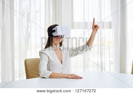 Young woman is smiling and pointing with her finger while watching something in virtual reality glasses