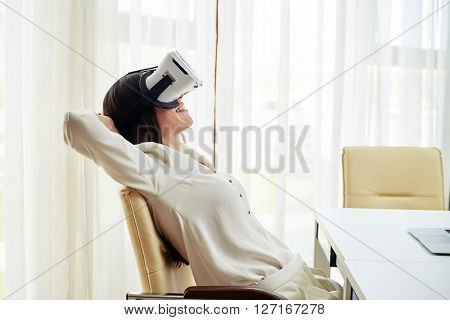 Young pretty woman in close-up  is smiling and feels relaxed while watching something in virtual reality glasses