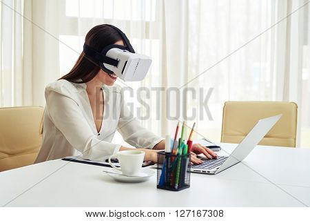 Young pretty woman is typing and watching something in virtual reality glasses while working on her laptop with cup on the table