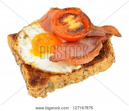 Fried egg and bacon rashers with grilled tomatoes on toast isolated on a white background