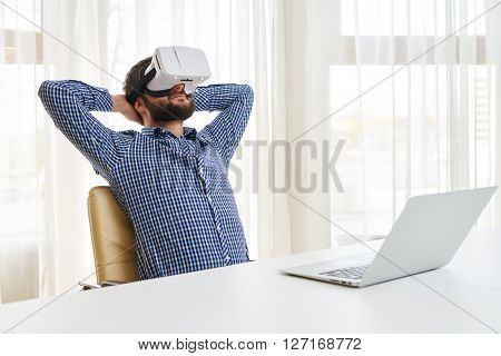 Young handsome man is relaxing spending pleasure time in 3d virtual glasses