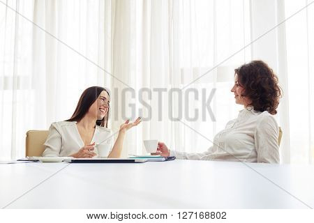 Two young smiling woman are sitting at the big white table working at the team and drinking coffee