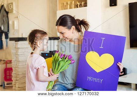 Mothers day, cute little girl giving flowers and greeting card to her mum