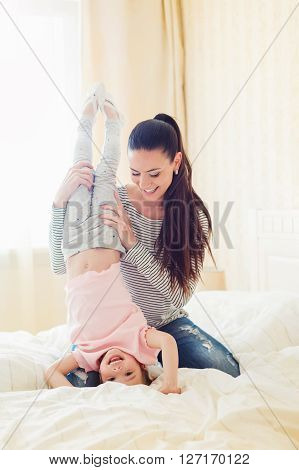 Beautiful young mother holding her daughter doing handstand in her bedroom