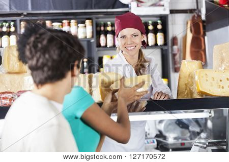 Happy Saleswoman Selling Cheese To Young Couple