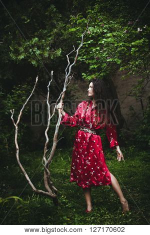 young woman in red kimono stand in garden holding big branch full body shot