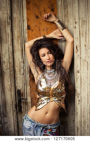 young woman lean on old door wearing boho style clothes glittering golden top and blue embroidered jeans