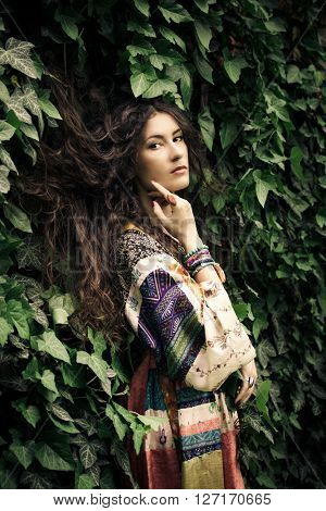 young  pensive long hair woman portrait in ivy wearing long silky dress