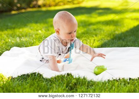 Happy baby boy with green apples on green grass in summer park. Healthy eating concept