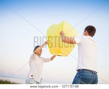 Young couple start a yellow Chinese sky lantern in the dusk near the sea