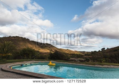 Swimming pool in a amazing hilly landscape underneath beautiful clouds