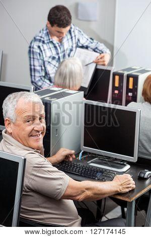 Portrait Of Happy Senior Man Using Compute In Classroom