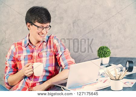 Smiling caucasian male with coffee sitting at wooden office table with various items looking at laptop screen