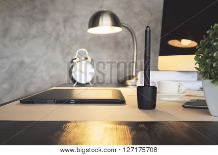 Sideview of desktop with graphic tablet plant alarm clock illuminated lamp and computer. Concrete wall background