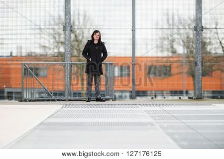Feminine Man Standing In Front Of Iron Fence In Industrial Area