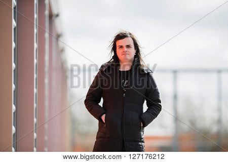 Androgynous man wearing black coat next to garages