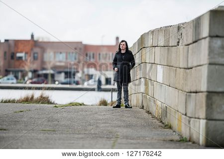 Androgynous man wearing black coat standing near concrete wall