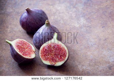 Fresh ripe organic figs on brown background