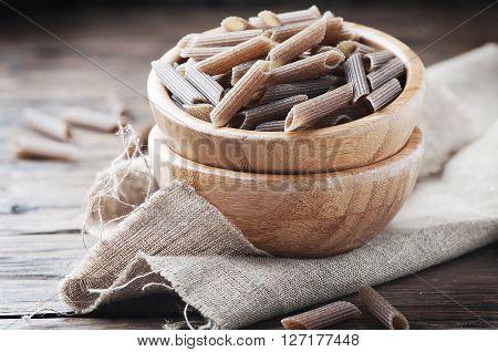 Uncooked Buckwheat Pasta On The Wooden Table