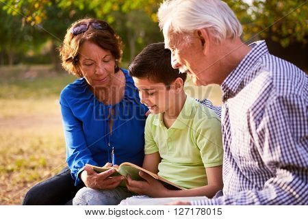 Grandparents educating grandson: Senior woman and old man spending time with their grandchild in park. The old people help the preteen kid studying and doing his school homework