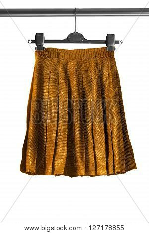 Pleated golden shiny skirt on clothes rack isolated over white