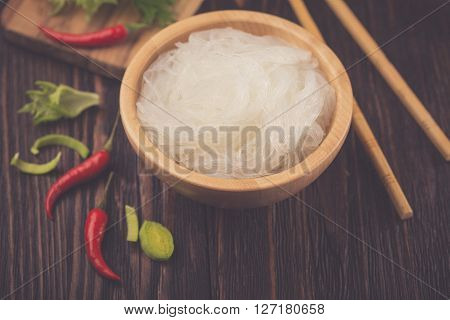 Ingredients of Asian cuisine - rice noodles leek lettuce red hot pepper on a dark wooden background ** Note: Visible grain at 100%, best at smaller sizes